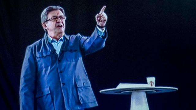 Jean-Luc Mélenchon steht als eine Art Hologram auf der Bühne.