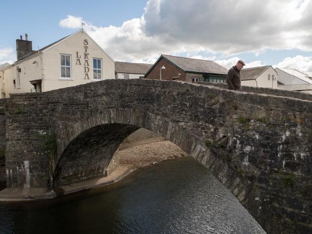 Eine Bogenbrücke aus Stein, die von einem alten Mann überquert wird.