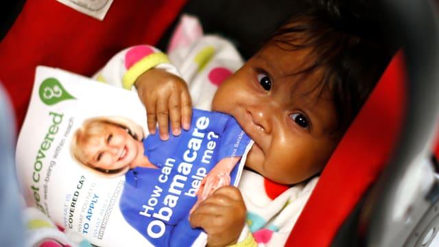 Kind knabbert an Obamacare-Broschüre.
