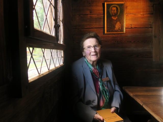 Frau in der Kapelle Bruder Klaus mit Bibel in Hand