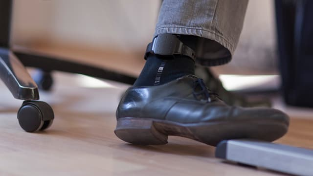 Ein Mann trägt am Knöchel eine elektronische Fussfessel.