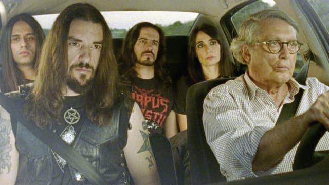Film-Still aus «Technoboss»: Protagonist sitzt mit Metal-Band im Auto.