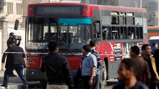 Menschen an einem demolierten Bus