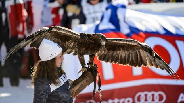 Das Bild zeigt eine Frau, die einen Adler hält.