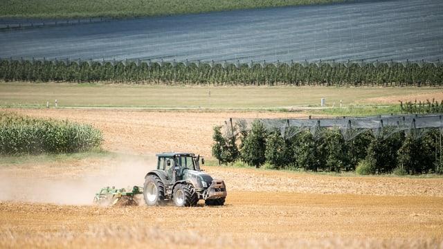 Ein Traktor fährt auf einem Feld. Der Boden ist sehr trocken.