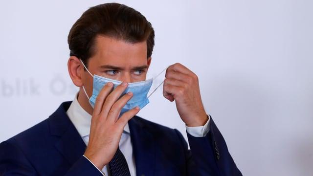 Kanzler Kurz zieht eine Maske an.