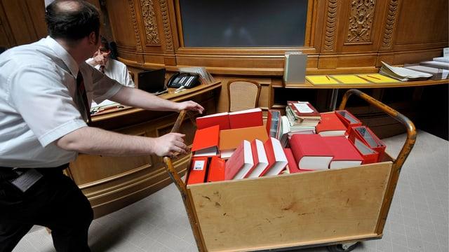Ein Mann schiebt einen karren voll mit roten Büchern durch den Nationalratssaal.