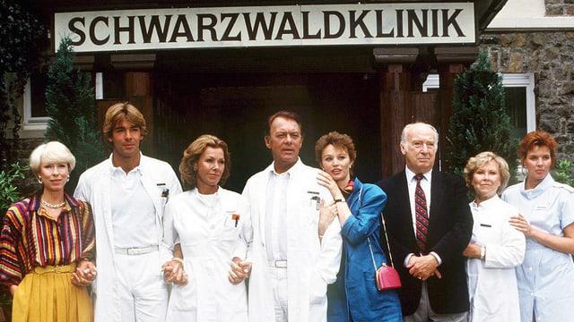 Gruppenfoto von Schauspielern in Ärztekleidung, darüber ein Schild mit der Aufschrift SCHWARZWALDKLINIK.