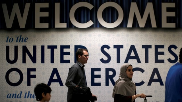 Plakat «Willkommen in den USA» in einem Flughafen.