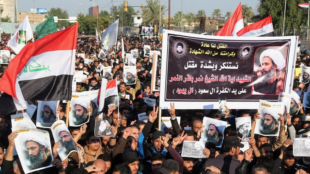 Fulla da glieud che demonstrescha cun plactats dal spiritual Nimr al-Nimr e bandieras da l'Irak.