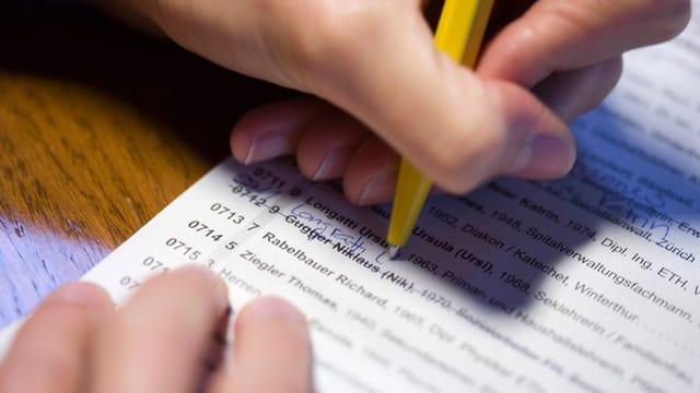 Hand mit Kugelschreiber streicht Namen auf Wahlzettel.