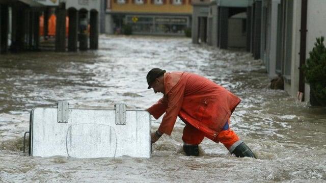 Ein Arbeiter kämpft gegen Hochwasser auf einer überschwemmten Strasse.