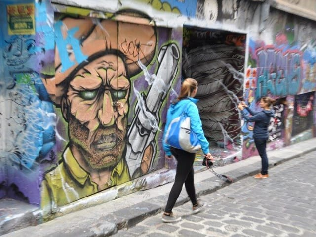 An den Hauswänden Graffitis, eine junge Frau fotografiert ein Bild.