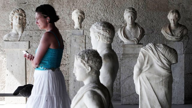 Eine Torusitin zwischen antiken Statuen in einer Ausstellung in Athen.
