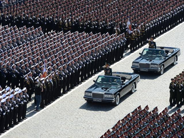 Zwei Autos fahren an stehenden Soldaten vorbei.