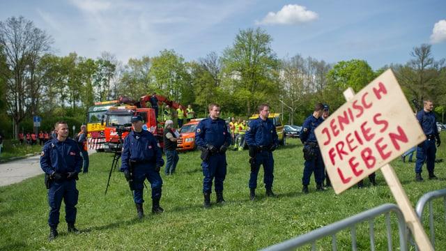 Eine Reihe Polizisten auf einer Wiese, im Vordergrund ein Schild mit roten Lettern: «Jenisch freies Leben»
