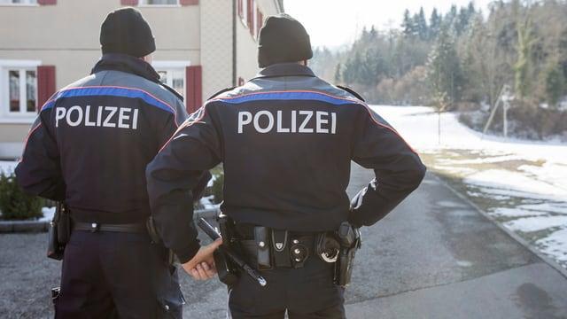 Zwei Polizisten der Luzerner Polizei von hinten betrachtet.