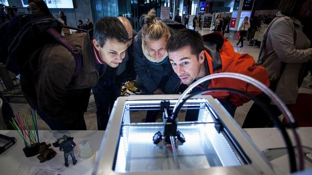 Drei Personen betrachten einen 3D-Drucker