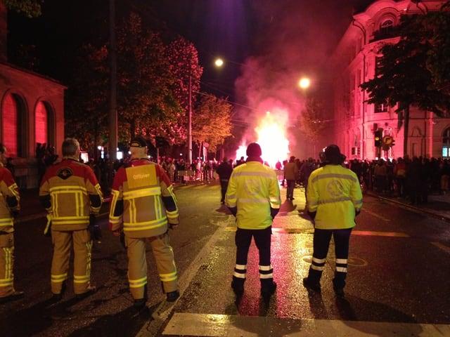 Männer in gelben Schutzanzügen, im Hintergrund brennen rote Fackeln