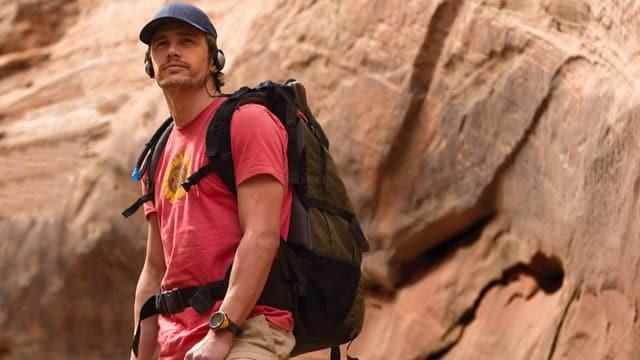 Ein Wanderer vor einer Felswand.