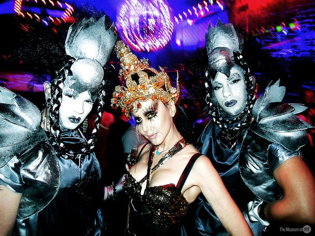 Kostümierte Frau umgeben von zwei Männers in futuristischen Kostümen.