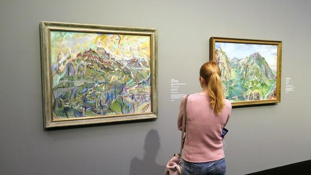 Eine Frau steht vor zwei Landschaftsbildern