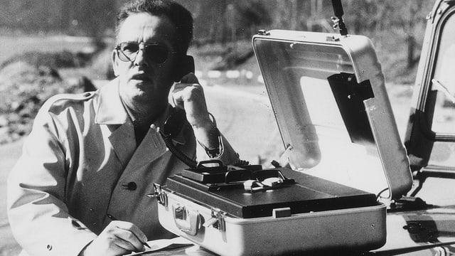Mann telefoniert an Telefon im Koffer.