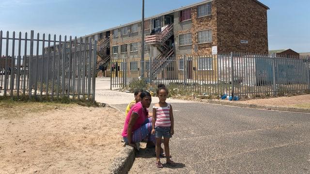 Familie auf Strasse vor Wohnblock