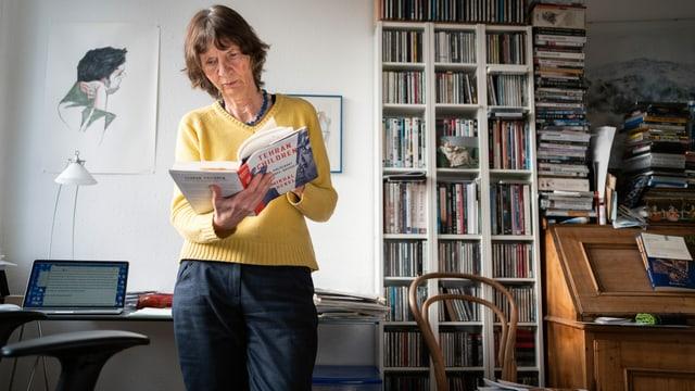 Aleida Assmann in ihrem Büro, ein Buch in ihrer Hand.