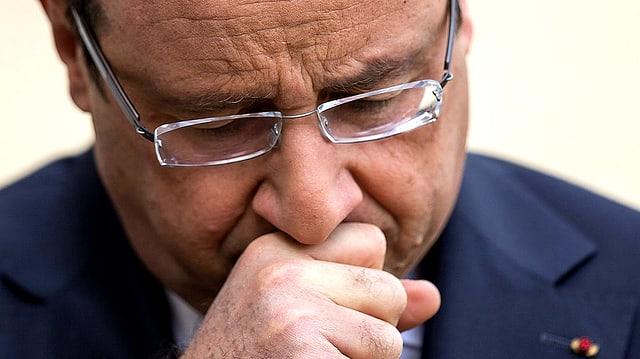 Nahaufnahme des französischen Präsidenten François Hollande. Er hält sich die Faust auf den Mund.