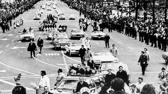Wagenkolonne von Nixon auf einer grossen, menschengesäumten Strasse, aus dem vordersten Auot winken stehend Nixon und seine Gattin