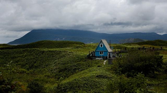 Grüne, hügelige Landschaft, darin steht ein blaues Holzhäuschen.