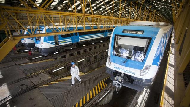 Weiss-blaue Züge in einem Hangar.