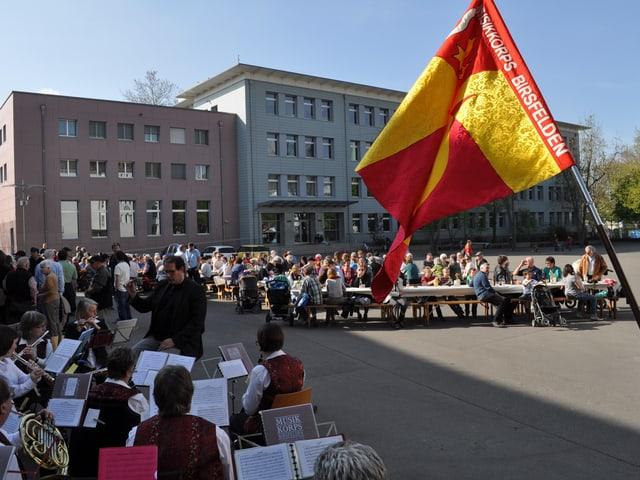 Im Vordergrund spielt das Musikkorps, im Hintergrund sitzen Besucher des Banntags an Holztisch-Garnituren.