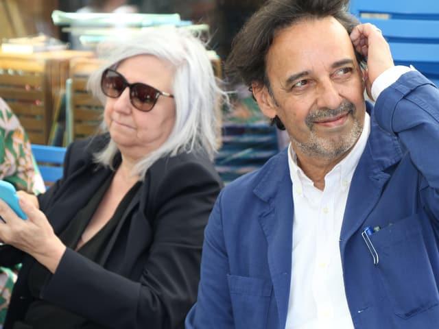 Ein Mann mit weissem Hemd, blauem Jackett und braunen Haaren. Links von ihm eine Frau mit langen grauen Haaren, Sonnenbrille, schaut aufs Handy.