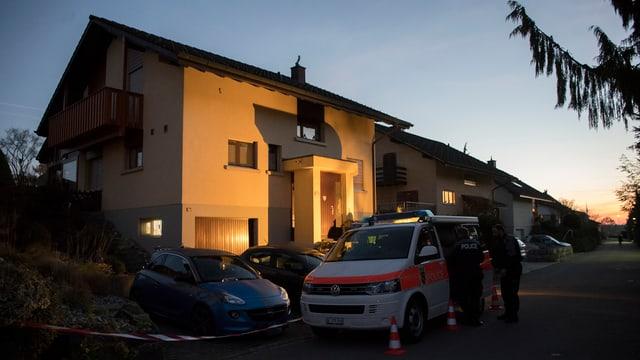 Ein Einfamilienhaus, davor steht ein Polizeiauto.