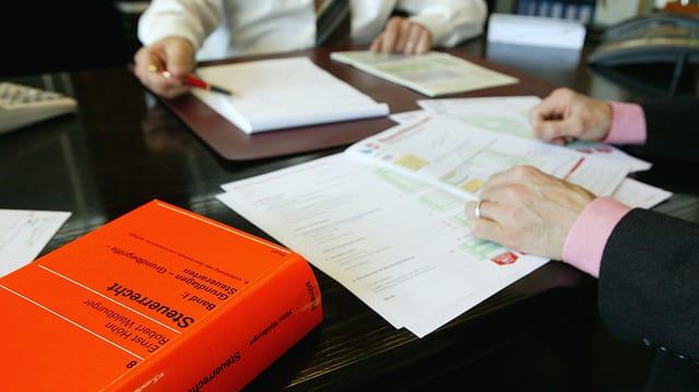 Zwei Männer brüten über einer Steuererklärung