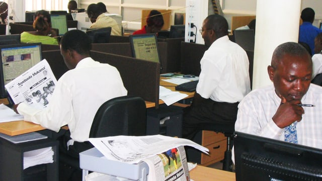 Schwarze Männer in einem Newsroom. Sie lesen oder arbeiten am Computer.