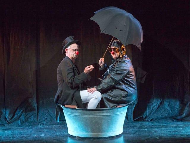 Ein Mann und eine Frau sitzen in einem Wäschezuber, sie hält einen Schirm in der Hand.