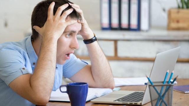 Mann sitzt erschreckt an seinem Laptop.