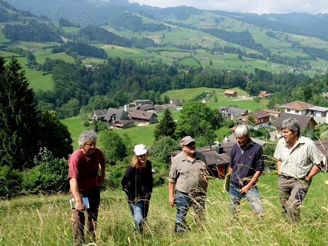 Fünf Menschen stehen im Halbkreis auf einer Wiese, im Hintergrund Hügel