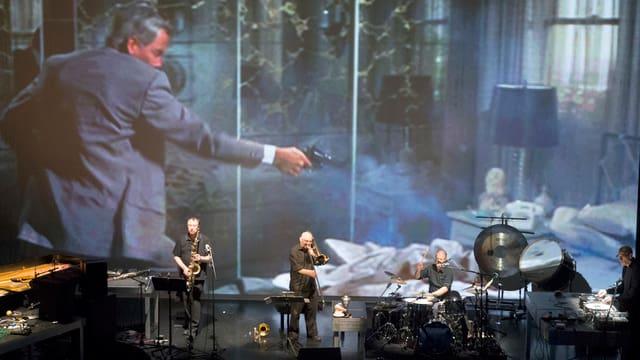 Bühne mit grosser Leinwand - vorne ganz klein vier Musiker.