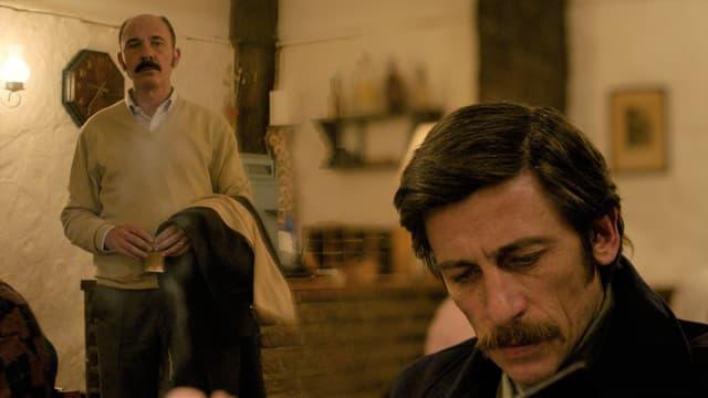 Ein Mann mit Schnauz sitzt im Wohnzimmer. Weiter hinten ist ein anderer, stehender Mann sichtbar, der nach Vorne schaut.
