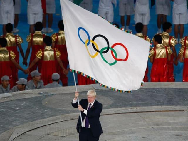 La bandiera olimpica vegn purtada en il stadion.