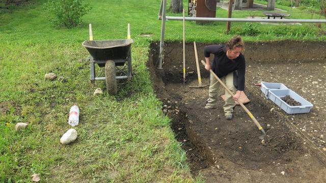 Frau mit Schaufel bei Ausgrabung.