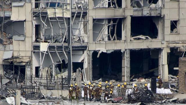 Zerstörtes Gebäude auf dem Hafengelände mit Rettungskräften in gelben Helmen davor