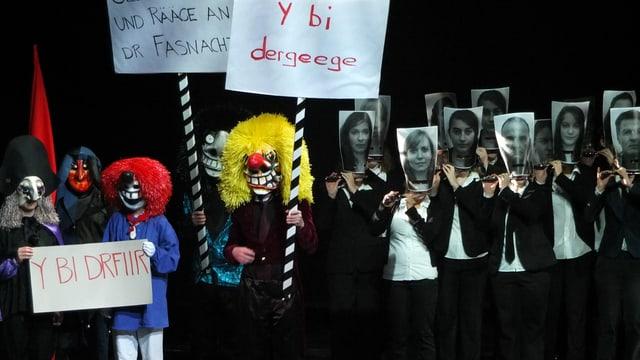 Farbige Waggis mit Transparenten, daneben schwarze Pfeiffer mit einer grossen Foto vor dem Gesicht
