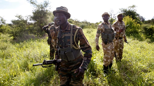 Männer mit Gewehren in Tarnkleidung.