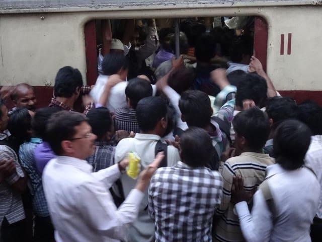 Menschen drängen in einen engen Zugseingang in Mumbai. Es hat keinen Platz.