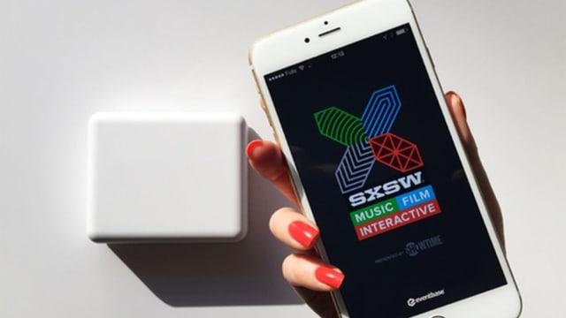 """Smartphone mit der SXSW App, Text: """"Music, Film, Interactive""""."""